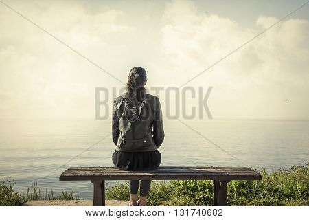 lonely girl sitting on the bench and looking at the sea.