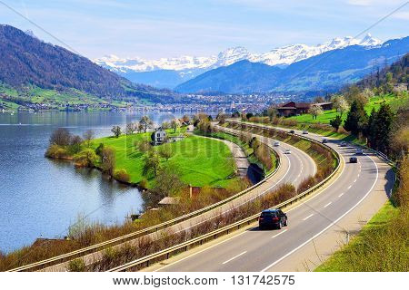 Swiss Landscape With A Highway, Lake And Mountains