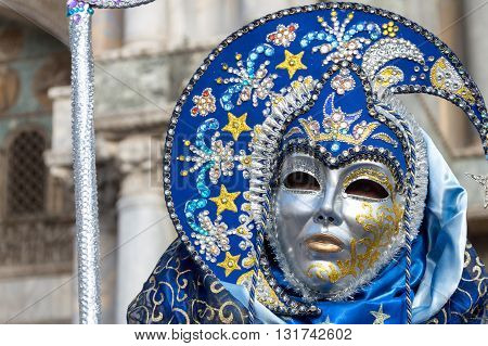 Venice, Italy - February 15, 2015: An unidentified person wearing a beautiful blue costume and a silver mask during the Carnival of Venice, in Italy.