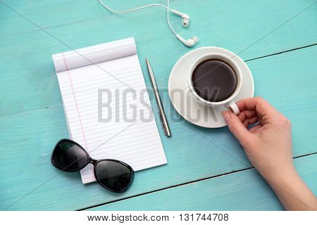Sunglasses, coffee, to-do list on a mint table. Open notebook with white page.