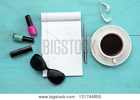 Sunglasses, coffee, to-do list on a aquamarine table. Open notebook with white page.