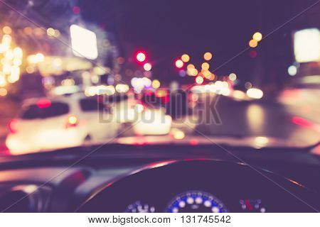 Blur image of inside cars with bokeh lights from traffic jam on night time. view from inside a car