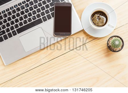 Office desk table with laptop computer coffee cup and smart phone. Top view with copy space