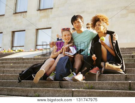 cute group of teenages at the building of university with books huggings, diversity nations, back to school