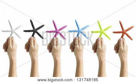 COLLECTION OF HANDS HOLDING STARFISH IN VARIOUS COLORS ON WHITE BACKGROUND