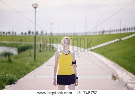 Young woman portrait in sport's clothes. Girl in yellow shirt