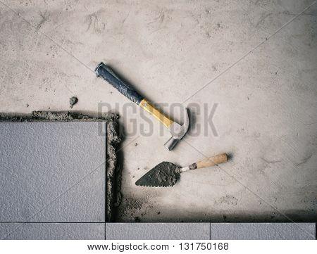 hammer on floor tile installation (Filtered image processed vintage effect )