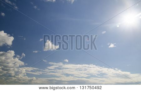 Open sky with clouds aerial view. Flight in deep blue summer sky bright sun with lens flare natural effect