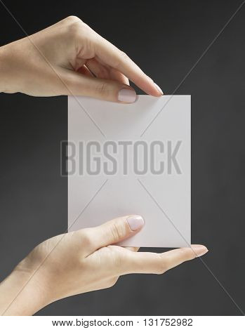 WOMAN'S HAND , HOLDING A WHITE EMPTY CARD , ON BLACK HIGHLIGHTED  BACKGROUND