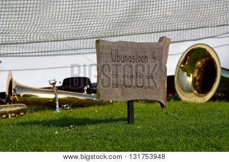 Brass instruments and instruction on the golf course sign