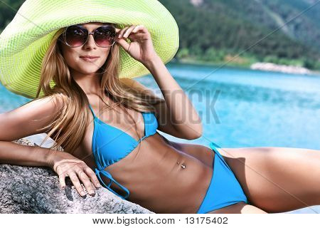 Beautiful young woman in bikini posing on a sea beach.