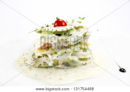Herring salad with avocado sauce on a plate in a restaurant