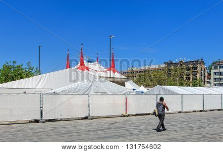 Zurich, Switzerland - 26 May, 2016: a person passing along the fence of Circus Knie temporarily installed on Sechselautenplatz square. Circus Knie is the largest circus of Switzerland, based in Rapperswil.