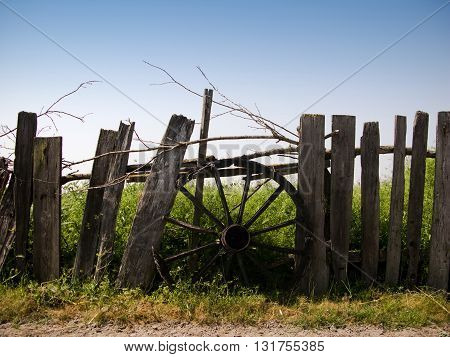 horizontal front view of an old chariot wheel covering the hole in a wooden fence with a green field behind