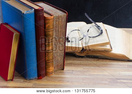 Old Books and glasses on wooden table desktop