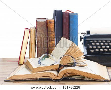 Old books, glasses and typewriter over white background - writting and publishing concept