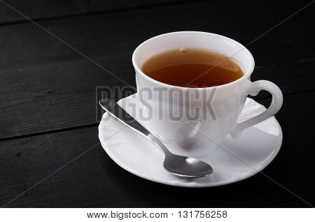 Teacup with spoon on black wooden background