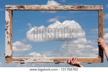 horizontal front view of a wooden frame kept with two hands against a blue sky with clouds