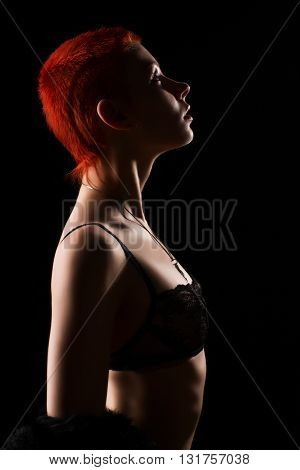 Young woman with short red hair in fur and black lace. Low key studio shoot on black background
