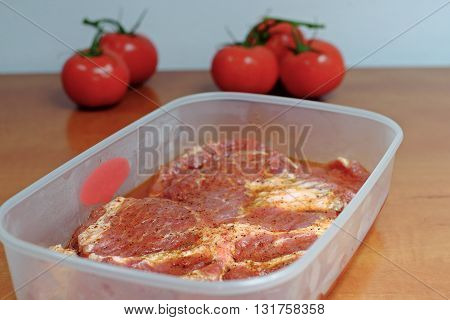 Raw marinated meat on a grill in a plastic bowl on wooden table with tomatoes in background party