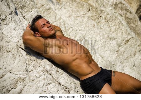 Attractive young man laying naked on white rocks, eyes closed, wearing only black swimming suit