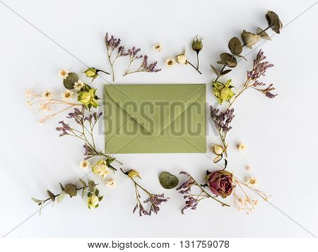 Frame of dry flowers and envelop on white background. Flat lay,