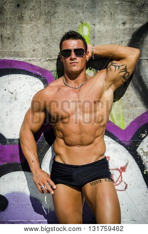 Attractive young muscle man laying naked on colorful wall, with eyeglasses, wearing only black swimming suit