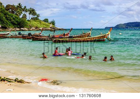 Phuket Thailand - October 27 2013: Children cool off & play in sea near moored long-tail boats in front of sea gypsy (Chao Lay) village on Rawai beach on southern tip of Phuket southern Thailand.