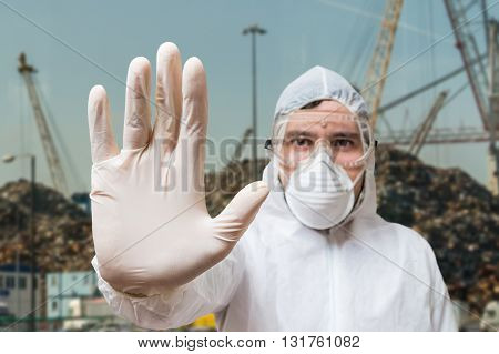 Technician In Coverall Showing Hand As Stop Gesture.