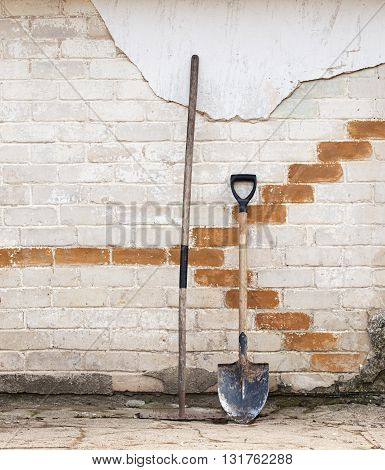 shovel and rake near the wall, ready for spring work in the garden