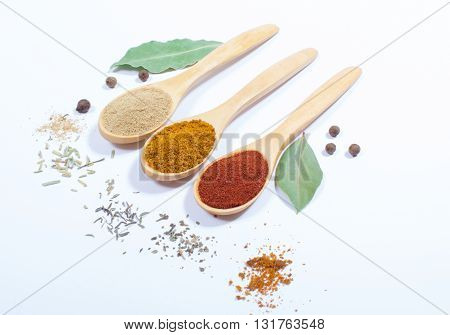 Spice powder isolated on white background. Paprika curry and ginger on a wooden spoon.