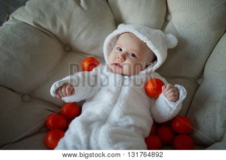 photo of cute baby with many tangerines