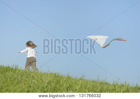 Girl child playing kite flying enjoying carefree childhood