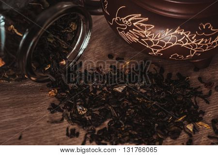 Asian teapot with dragon on stand and jar with scattering of fruit tea