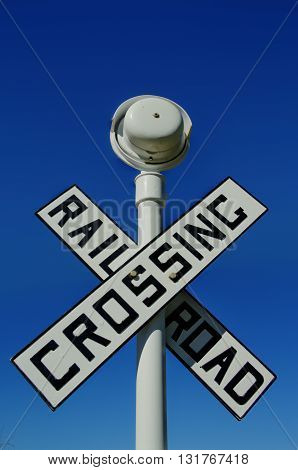 A rail road crossing sign with a clear sky in High Dynamic Range.