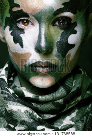 Beautiful young fashion woman with military style clothing and face paint make-up, khaki colors, halloween celebration close up