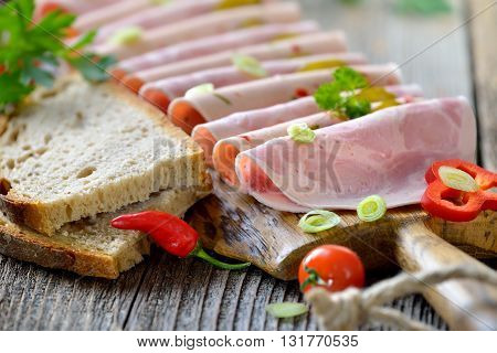Slices of Bavarian sausages  garnished and served with fresh farmhouse bread on a rustic wooden board