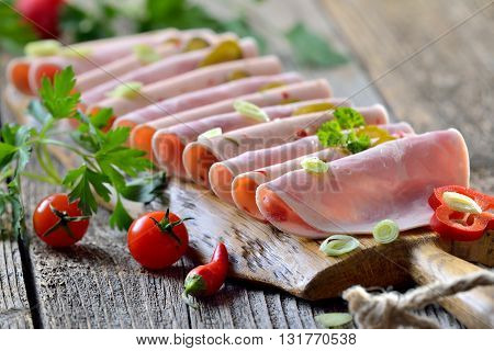 Slices of Bavarian sausages  garnished and served on a rustic wooden board