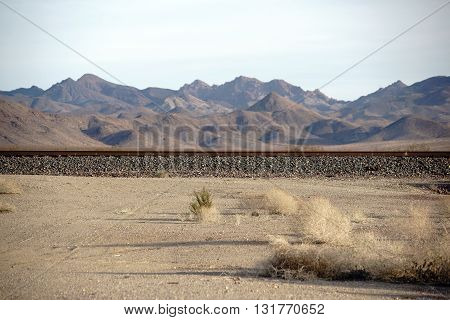 A railway line in the Mojave Desert with a mountain range in the background.