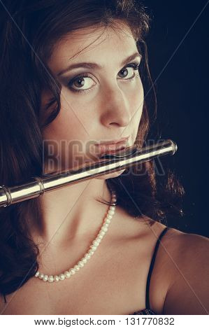 Woman Playing Transverse Flute On Black.