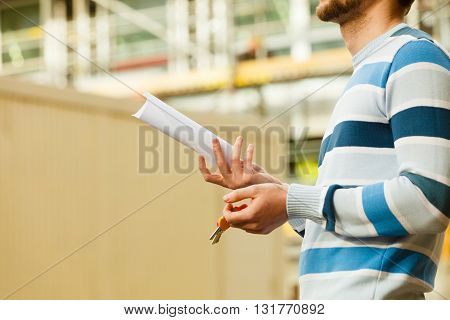 Finances business contract bills debt concept. Young man carrying keyring with documents. Male holding keys with papers.
