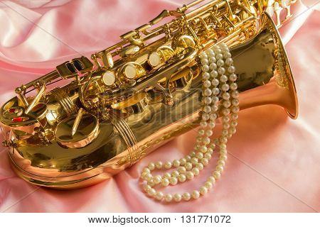 Saxophone and Pearl necklace on Pink silk fabric soft
