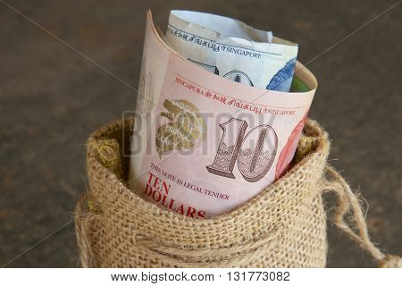 Singaporean money in a brown hessian bag.