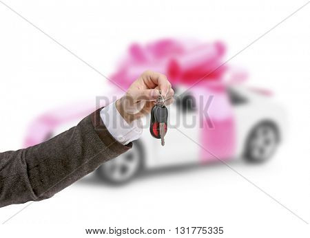 Male hand holding car keys against car background