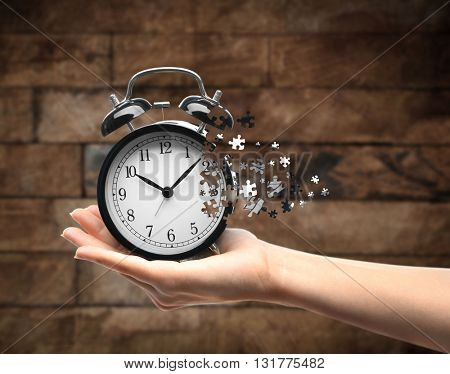 A retro alarm-clock on female hand on wooden background. Lost time concept