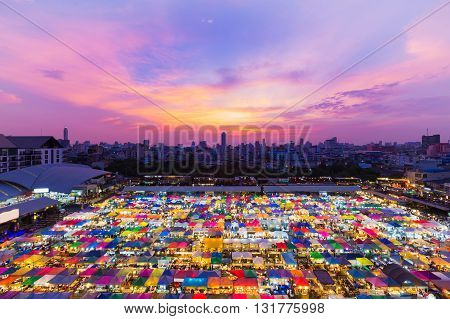 Aerial view, dramatic sky background after sunset over night market rooftop and city downtown background