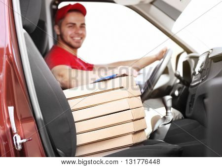 Young handsome man delivering pizza in car