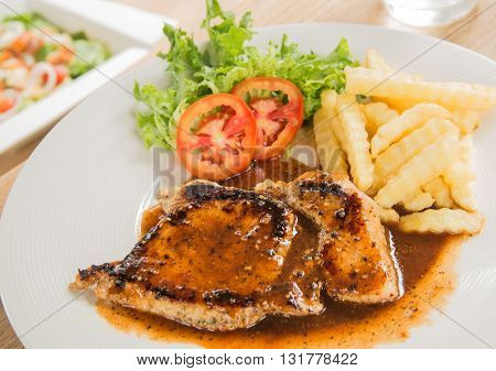 Pork steak in White plateGlass of waterFrench fries placed on wooden table.