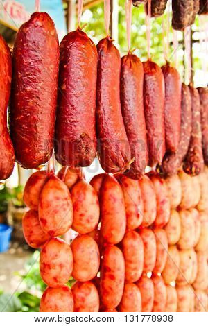 Home made meat salami sausage at street market hanging in line under sunlight to make good tasty
