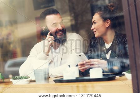 Picture of happy couple using phones in restaurant
